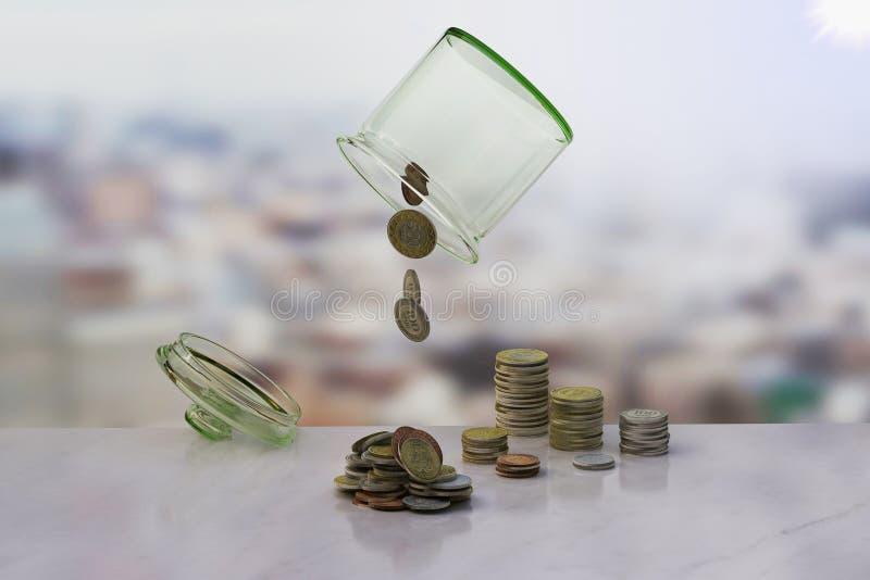 Uppochnervänt kruset av mynt på träbackgroen arkivfoton