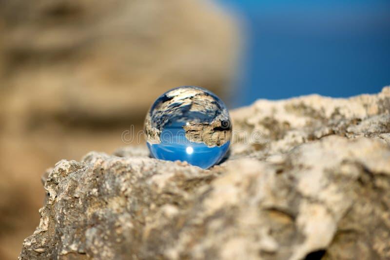 Uppochnervänt seascape med blå himmel och bevuxet med mossa vaggar - reflexion i en linsboll royaltyfria foton