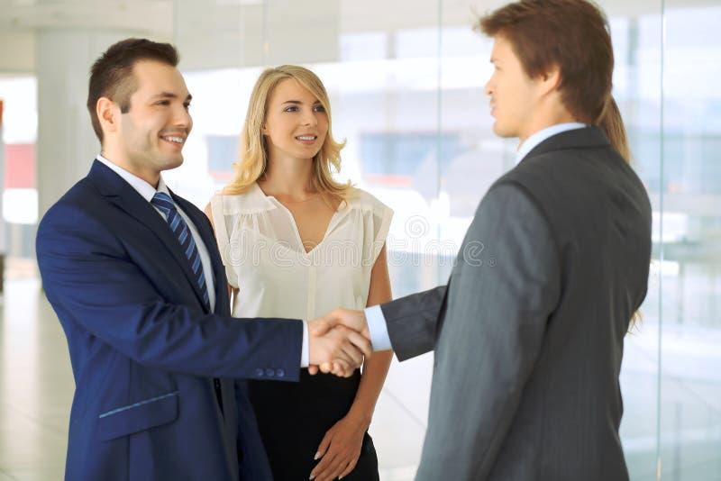 uppröra för affärsmanhänder Två säkra affärsmän som skakar händer och ler, medan stå på kontoret samman med royaltyfri fotografi