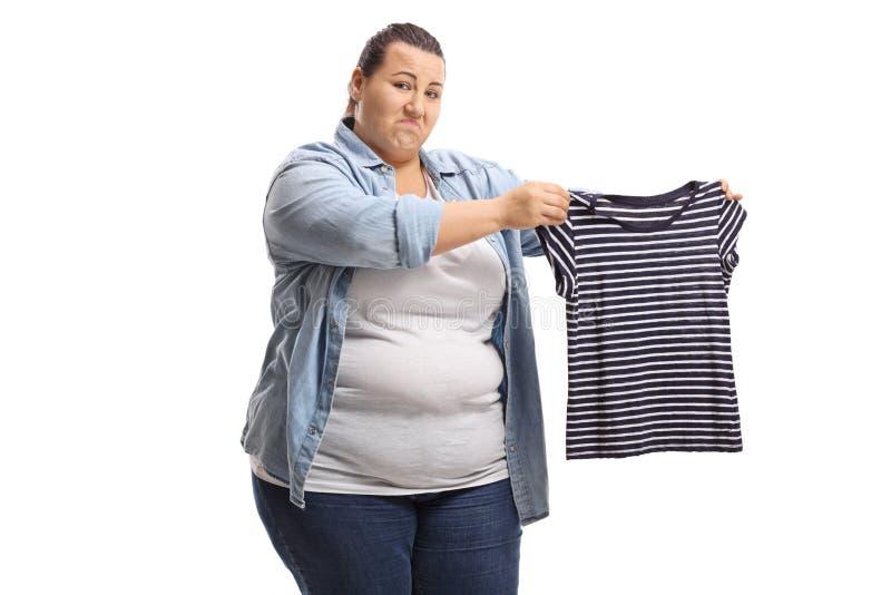 Uppriven överviktig kvinna som rymmer en krympt skjorta royaltyfri foto