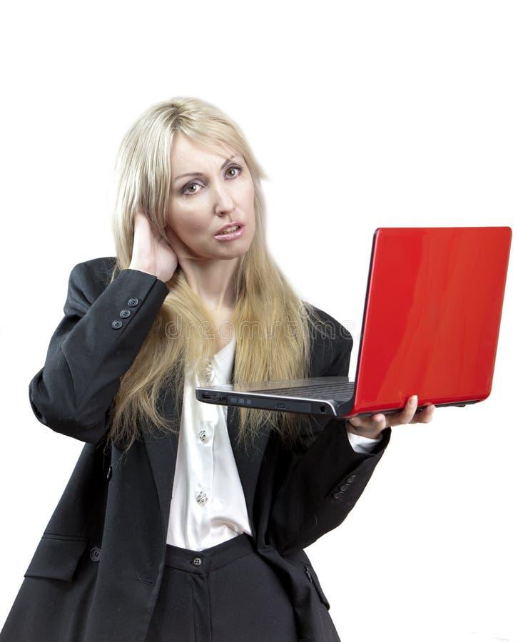 Uppriven affärskvinna med den röda bärbara datorn i händer royaltyfri foto