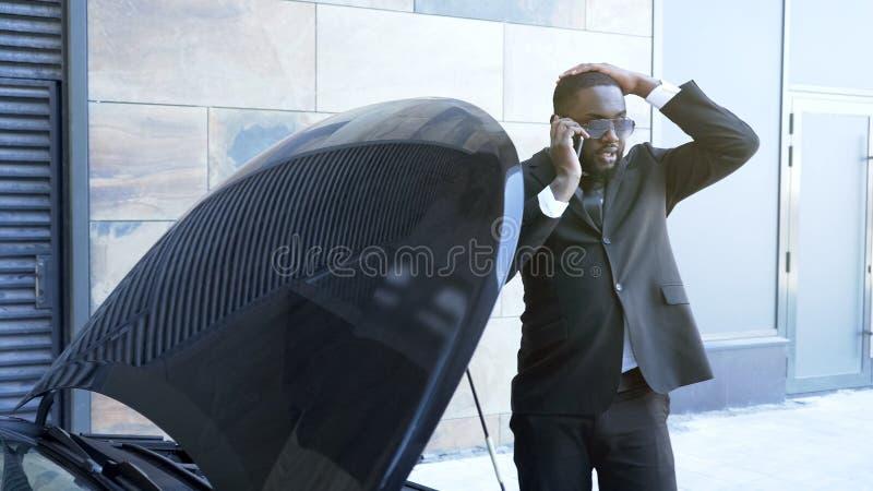 Uppriven affärsman nära den brutna bilen som kallar service för nöd- underhåll, problem royaltyfria foton