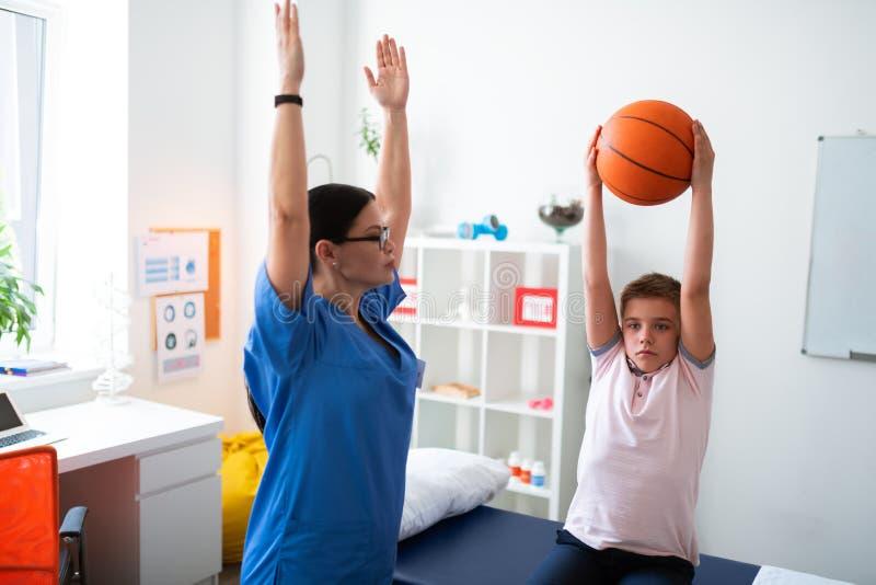 Uppriven arbetsam pojke som sitter i medicinskt kabinett och lyfter basketbollen arkivbilder