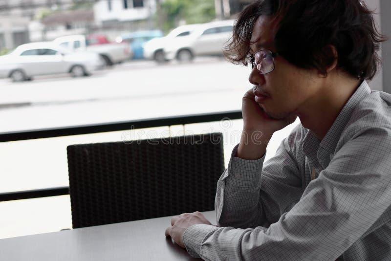 Uppriven arbetslös asiatisk man i fördjupningen som sitter i hem royaltyfria bilder