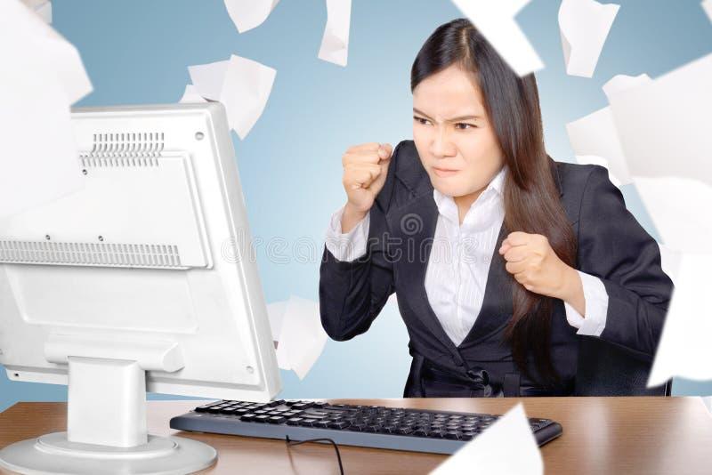Uppriven asiatisk affärskvinna, när arbeta med att flyga spritt papper arkivfoto