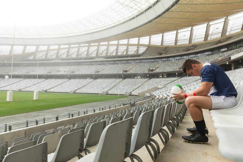 Uppriven Caucasian manlig rugbyspelare som sitter med rugbybollen i stadion arkivbilder