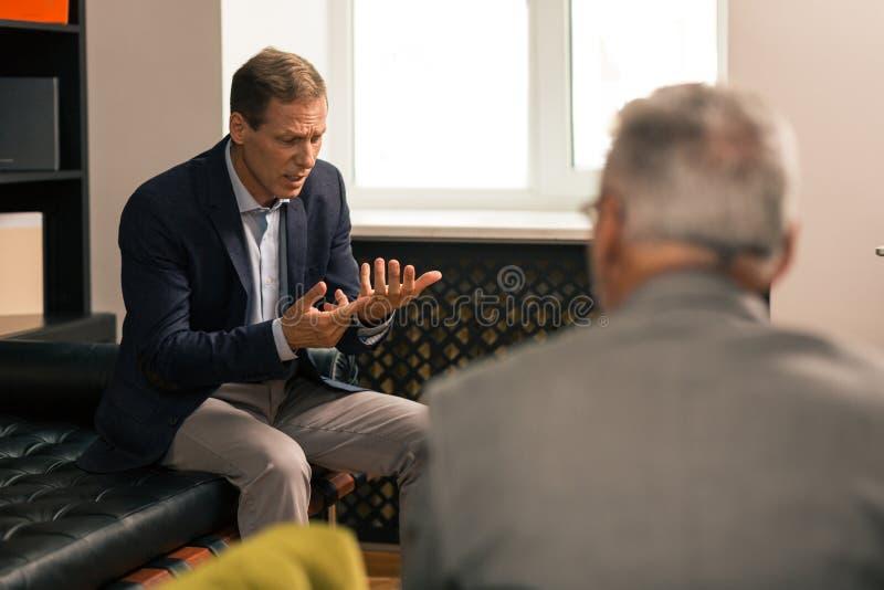 Uppriven gift brunhårig man som diskuterar hans personliga problem arkivbilder