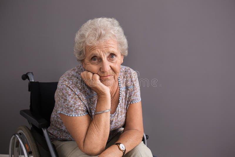 Uppriven hög kvinna i rullstol på grå bakgrund royaltyfri bild
