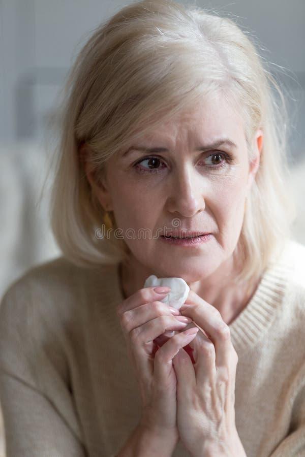 Uppriven hög kvinna som hemma gråter sorgsen känsla royaltyfri bild