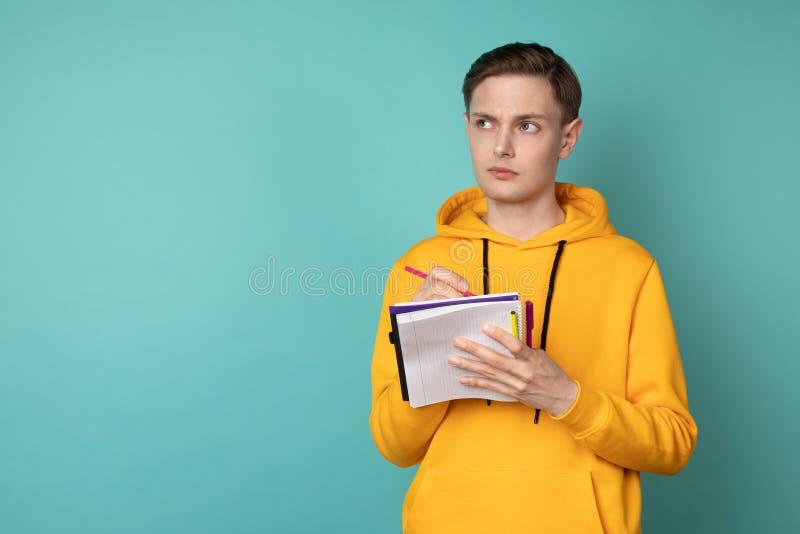 Uppriven h?rlig manstudent i tillf?llig kl?der som st?r mot den bl?a v?ggen med anteckningsboken och penna i h?nder arkivbild
