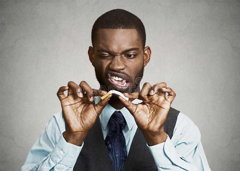 Uppriven ilsken affärsman som bryter cigaretten royaltyfri bild