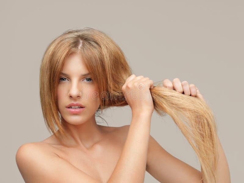 Uppriven kvinna som drar kluvna hårtoppar för torrt hår royaltyfri bild