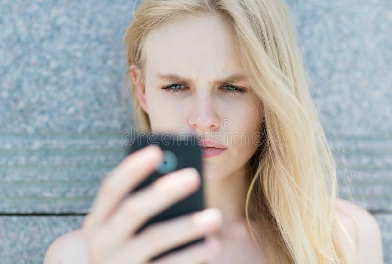 Uppriven kvinna som rymmer en mobiltelefon arkivfoton