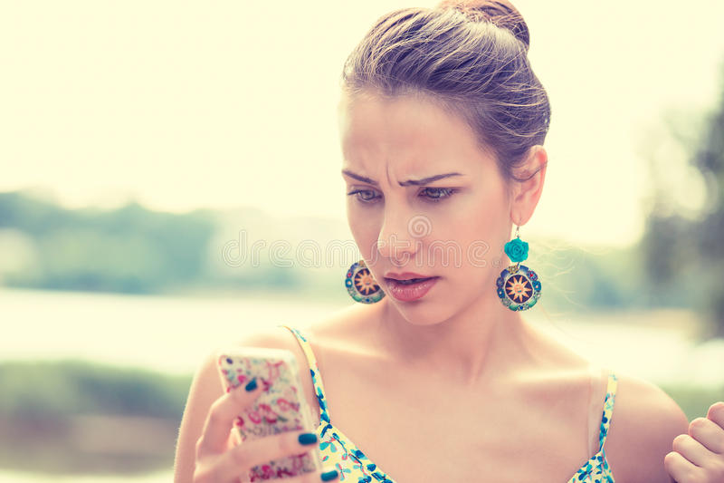Uppriven ledsen skeptisk olycklig kvinna som smsar på telefonen royaltyfria bilder