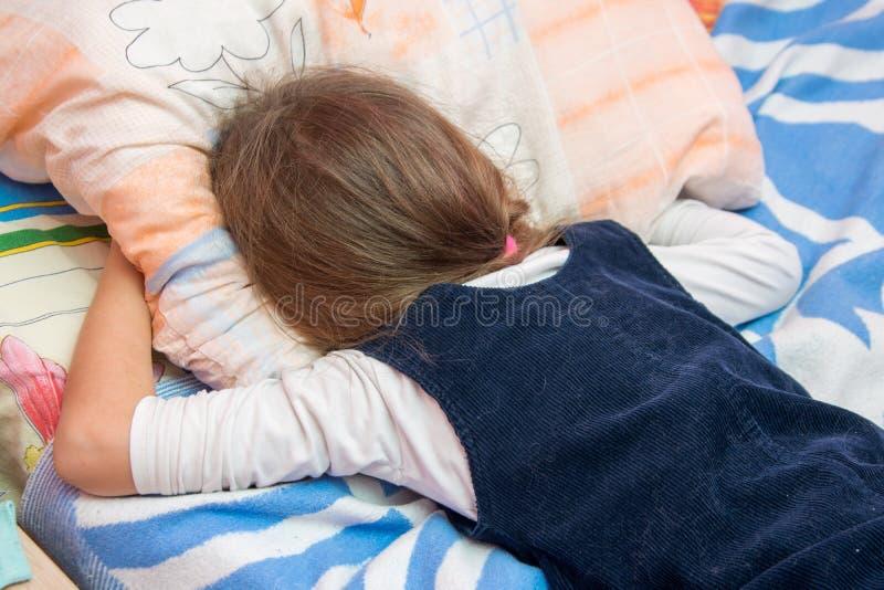 Uppriven liten flickagråt med hans framsida som begravas i kudde royaltyfri foto