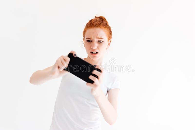 Uppriven ljust rödbrun kvinna i t-skjortan som spelar på hennes smartphone royaltyfria bilder