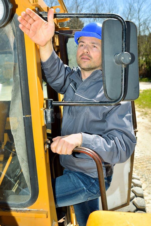 Uppriven man som kör den enorma traktoren arkivbilder