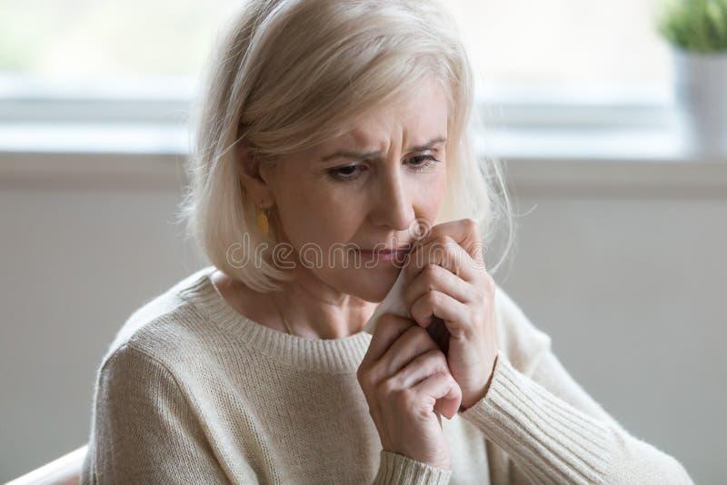 Uppriven mellersta åldrig kvinna som torkar revor som gråter känslig deprimerad lo arkivfoto