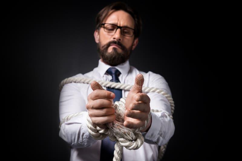 Uppriven mitt åldras affärsman i glasögon som står bundet med repet royaltyfria bilder