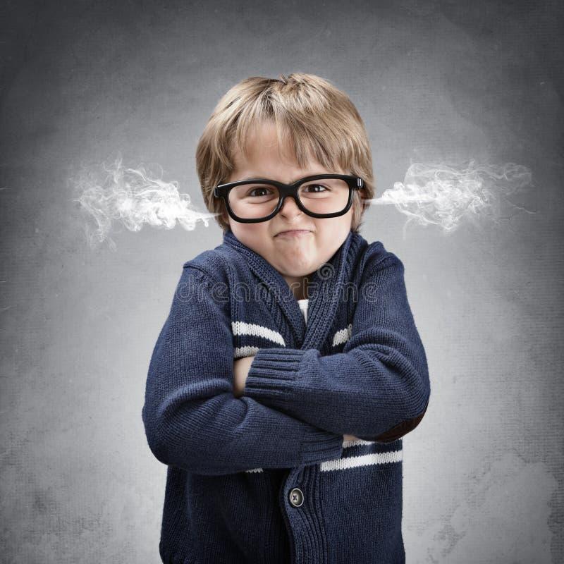 Uppriven och ilsken pojke som vädrar ånga från hans öron royaltyfria bilder