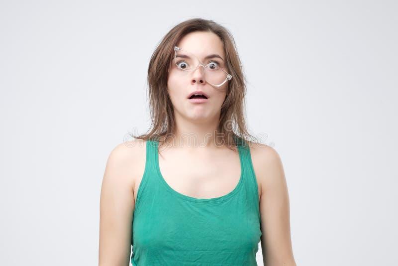 Uppriven stilig kvinna som är trött av bärande exponeringsglas Ledsen ung femalr som missar, i att sätta på glasögon arkivbild