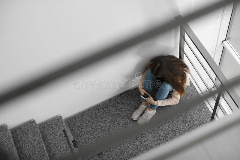 Uppriven tonårs- flicka med smartphonen som inomhus sitter på trappuppgång royaltyfria foton
