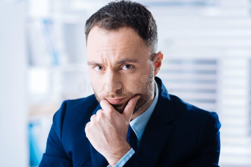 Uppriven ung affärsman som ser dyster, medan vara på arbete arkivbild