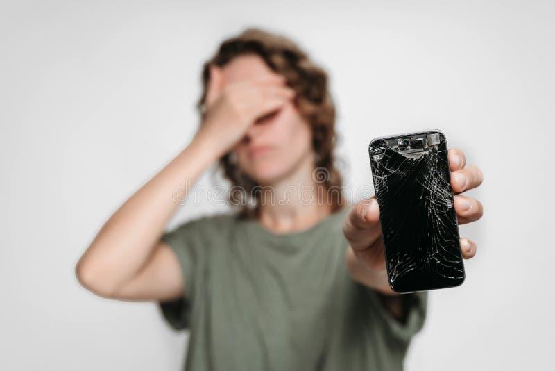 Uppriven ung kvinna som rymmer hennes brutna smartphone Telefonskärmbehov att reparera royaltyfri foto