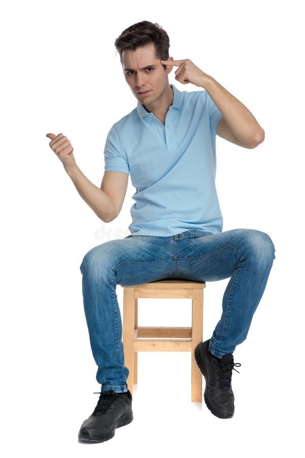 Uppriven ung man som pekar till hans panna och rynka pannan fotografering för bildbyråer