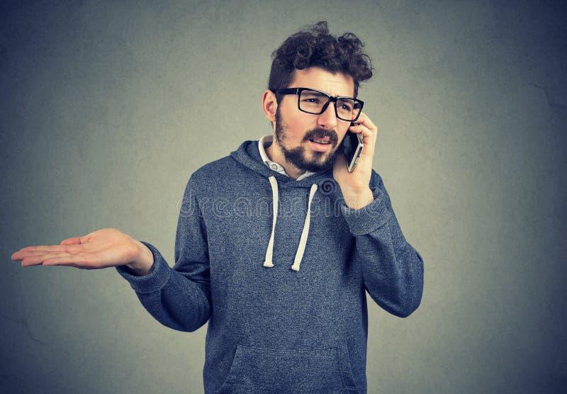 Uppriven ung man som talar på mobiltelefonkänsla som förargas och frustreras royaltyfria bilder