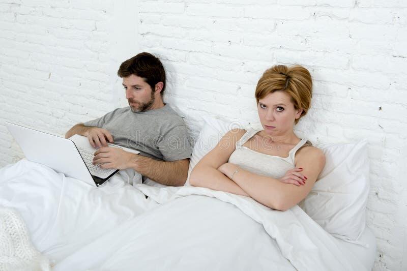 Uppriven unsatisfied för attraktiv kvinnakänsla och frustrerat i säng med hans make medan manarbetet på datorbärbara datorn som i arkivfoton