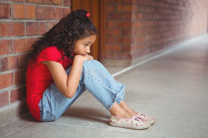 Upprivet ensamt flickasammanträde av henne royaltyfri foto