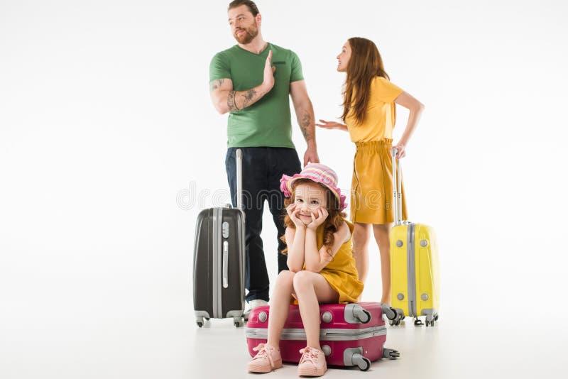 Upprivet sammanträde för litet barn på resväskan medan argumentera för föräldrar royaltyfria foton