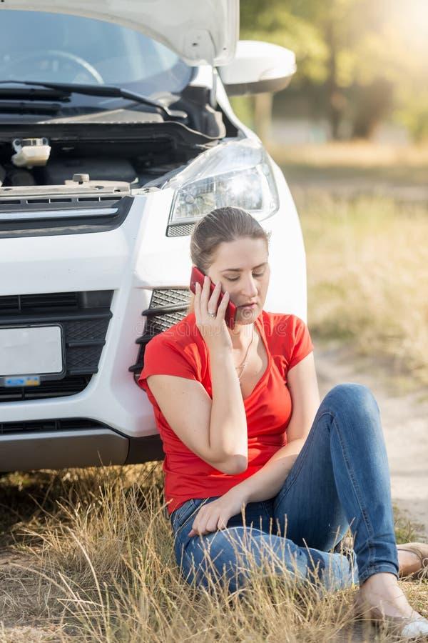 Upprivet sammanträde för ung kvinna på hennes brutna bil i fält och kallabärgningsbilen för hjälp arkivbild