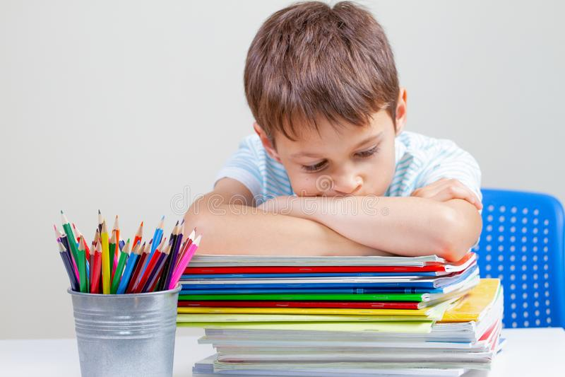 Upprivet skolpojkesammanträde på skrivbordet med högen av skolböcker och anteckningsböcker arkivbild