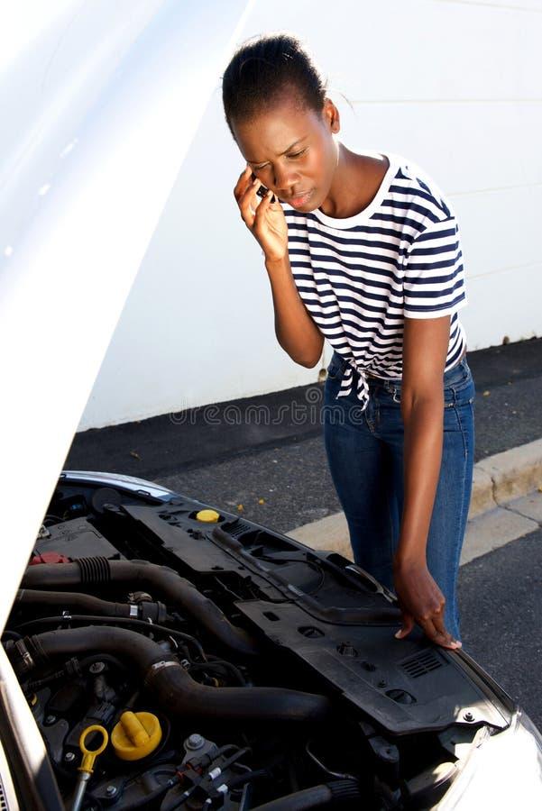 Upprivet ungt afrikanskt kvinnaanseende med den brutna ner bilen som parkeras på sidan av en väg och att kalla för hjälp royaltyfri foto