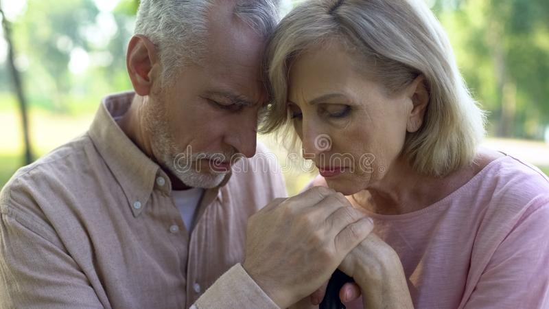 Upprivna gamla par som lutar på den gå pinnen, pensionsålderservice, armod royaltyfri foto