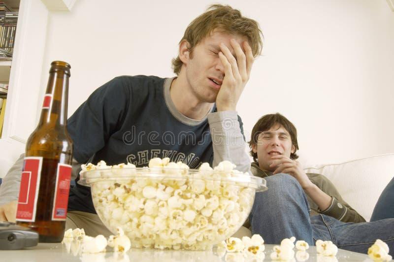 Upprivna män som håller ögonen på TV med popcorn och öl på tabellen fotografering för bildbyråer