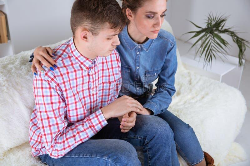 Upprivna par som hemma sitter Problem i parbegrepp arkivbilder