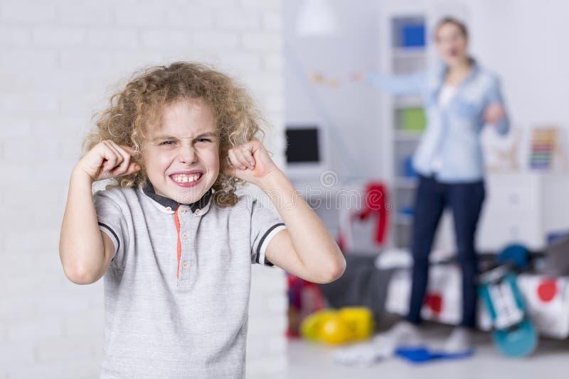 Upprorisk pojke som täcker hans öron fotografering för bildbyråer