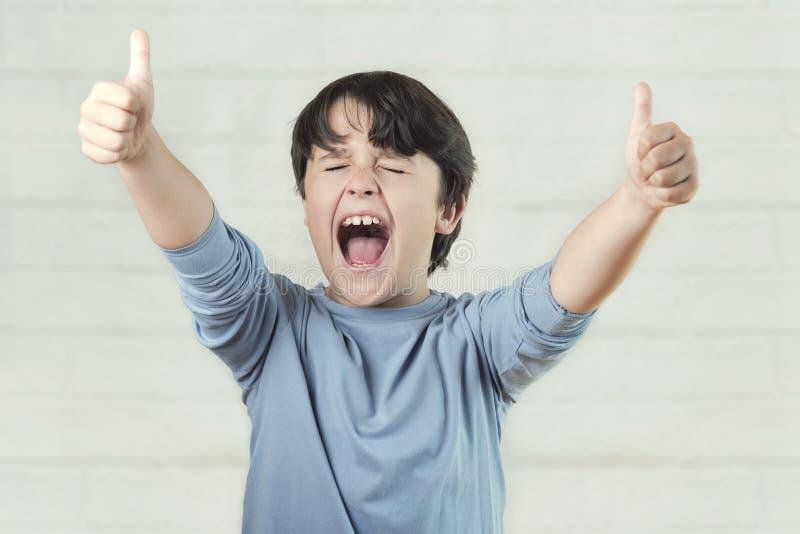 Upprymt barn som visar upp tummar arkivbild