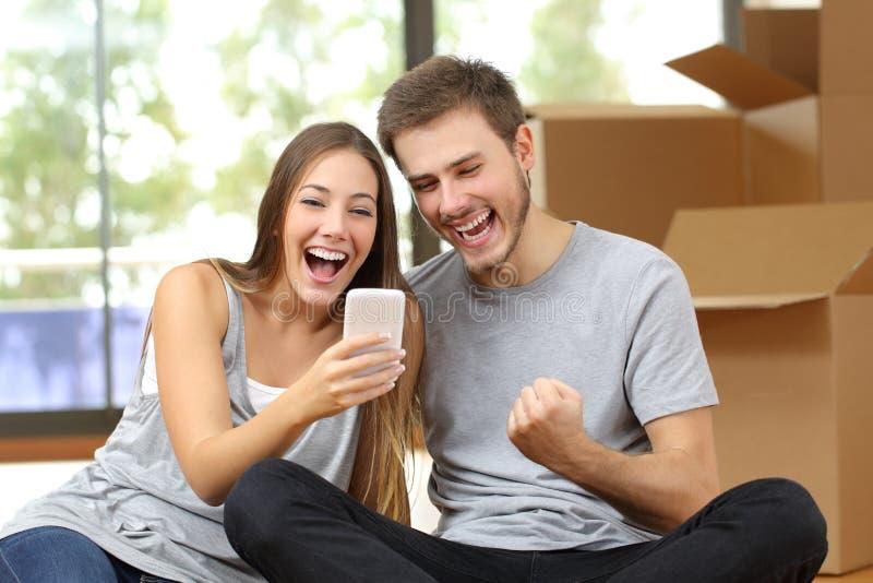 Upprymt parflyttninghus och hållande ögonen på telefon royaltyfri foto