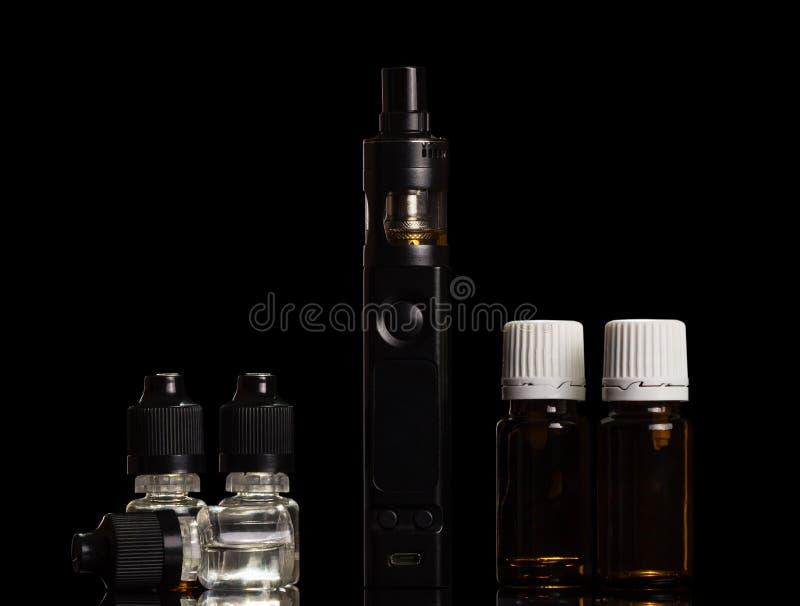 Uppsättning av aromatiska flytande för inhalation av ånga och av den elektroniska cigaretten som isoleras på svart royaltyfri fotografi