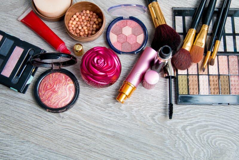 Uppsättning av dekorativa skönhetsmedel och borstar på grå träbakgrund Olika makeupprodukter Bästa sikt, ram kopiera avstånd royaltyfria foton