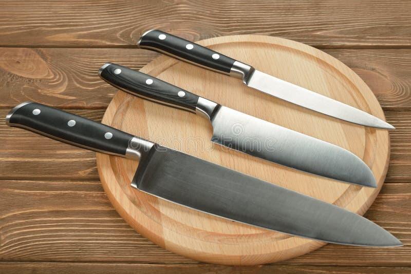 Uppsättning av den kökknivar och skärbrädan royaltyfri fotografi