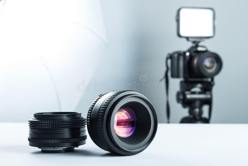 Uppsättning av DSLR-linser på en vit tabell i stuidio, mot bakgrunden av DSLR-kameran som ska tändas, och softbox arkivfoton