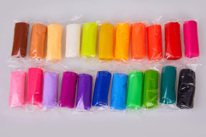 Uppsättning av färgrik plasticine som isoleras på en vit bakgrund arkivbilder