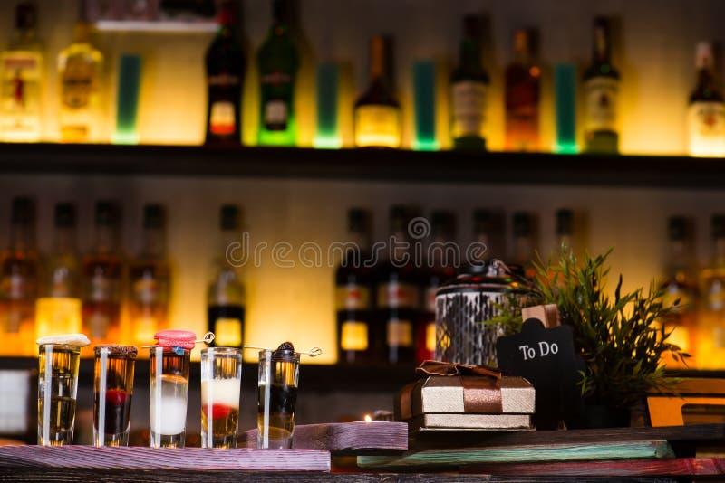 Uppsättning av färgrika alkoholiserade coctailar i skottexponeringsglas på suddighetsstång royaltyfria foton