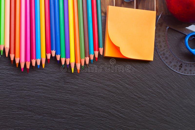 Uppsättning av färgrika blyertspennor på svart bräde royaltyfri foto