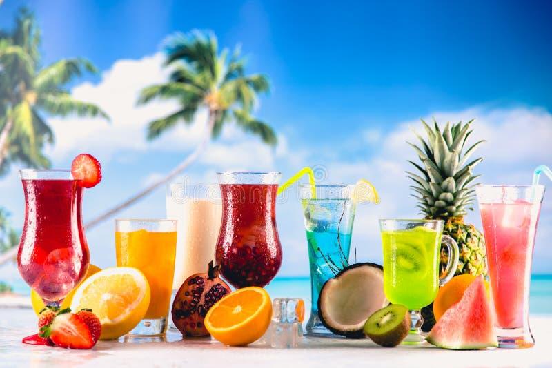 Uppsättning av färgrika drinkar i exotiskt landskap arkivfoton